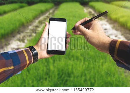 Hand holding blank smart phone and pen for Ecology Farming Agriculture business Environment Concept