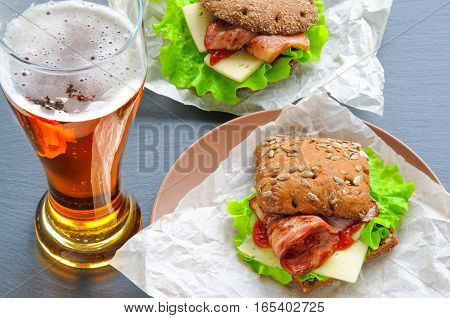 Glass of beer and two burger-like sandwiches with lettuce, bacon, cheese, ketchup on paper, plates and black slate stone