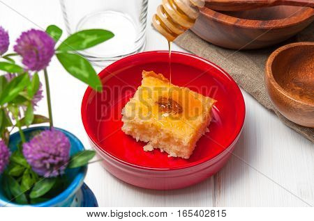 Basbousa - arabian cake with almonds and honey syrup in red bowl on white wooden background
