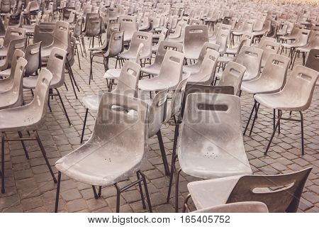 Many chairs outdoor. Gray plastic chairs. Place where citizens gather.