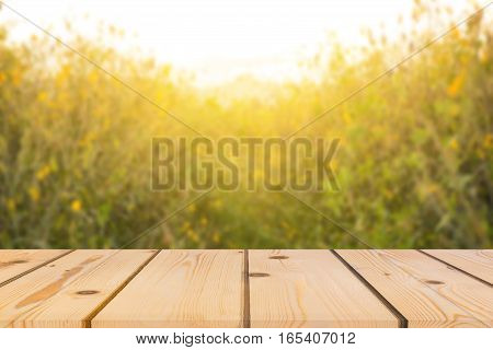 Wooden board empty table in front of background. Perspective brown wood over yellow flower can be used for display or montage your products. spring season. vintage filtered image.