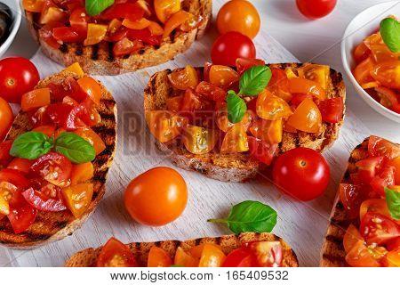 Tasty Traditional Tomato bruschetta with fresh basil on white board.