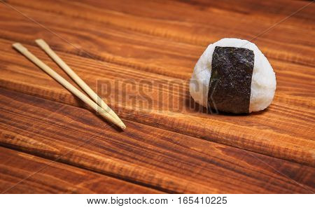 Japanese onigiri with chopsticks on wooden background. Rice ball with filling wrapped seaweed nori