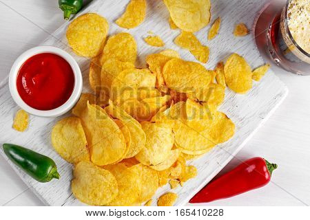 Gold and Crispy Potato Chips with hot sauce, beer on white board, background