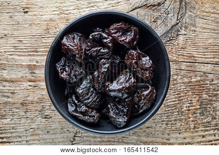 Bowl Of Prunes On Wooden Table, From Above