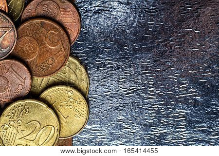 Pile of euro coins on the background of shiny foil copy space