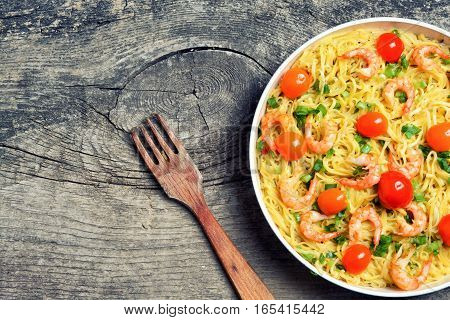 Pasta with shrimps & tomato on wooden background