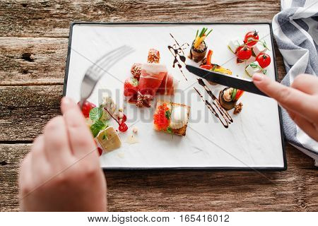Eating of appetizers with cutlery, eater pov. Top view on tray with delicatessen mix with knife and fork above it. Degustation, choosing tapas for party or wedding, event organization concept