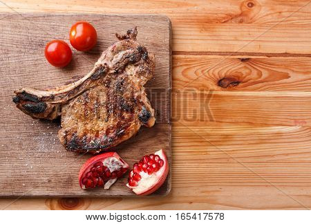Rib eye steak with tomatoes and pomegranate on chopping board with copy space aside