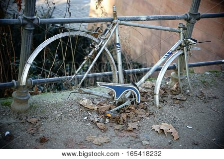 An old bicycle frame is chained and forgotten by a fence.
