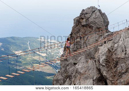 Scenic mountain landscape with girl on rope ladder