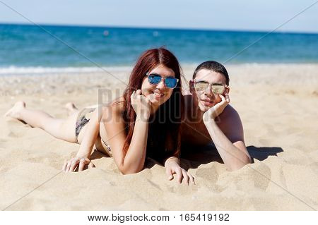Young couple resting on sandy sea beach warm day