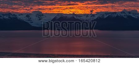 Kackemak Bay glows pink as the sun rises flinging golds and reds behind the Kenai Mountains.