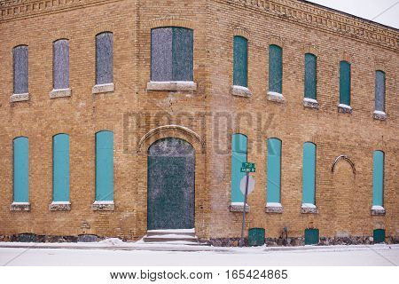 Historical two storied exterior brown brick building with rows of boarded up arched windows siding two streets