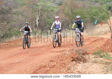 Smiling Family Enjoying Outdoors Ride At Mountain Bike Race