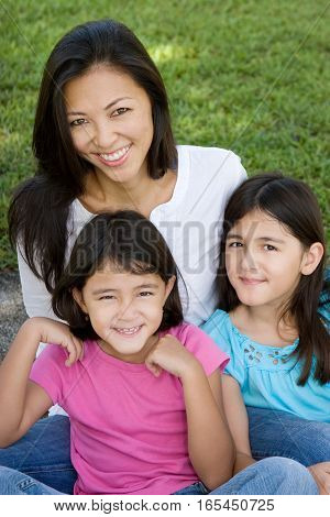Portrait of an Asian mother and her daughters.