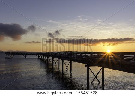 Ocean pier at daybreak with rising sun,clouds and an orange sky.Vancouver Island Canada