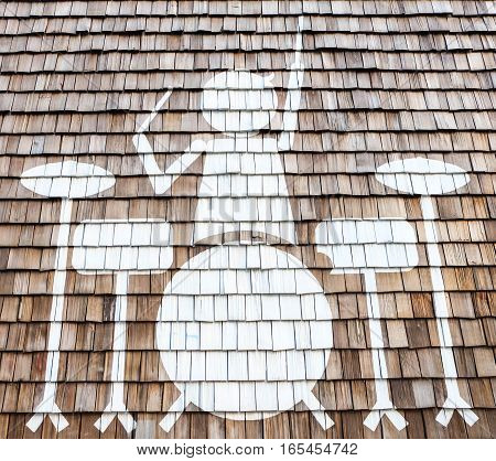 A man with drums on the wood wall or background