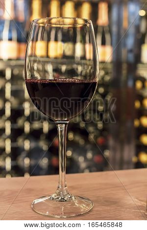 A glass of red wine in front of a blurred rack with many bottles. Selective focus