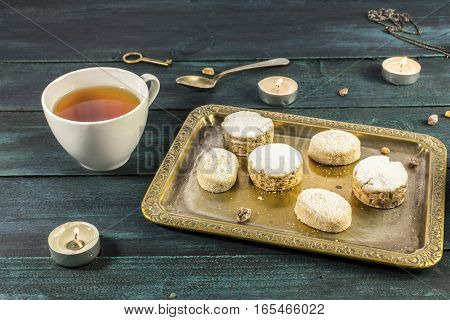 A photo of mantecados and polvorones, traditional Spanish cookies, on a vintage tray with a cup of tea and candles on a dark wooden background