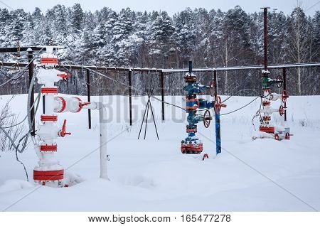 Wellhead valve. Oil and gas concept. Industrial site during winter period.