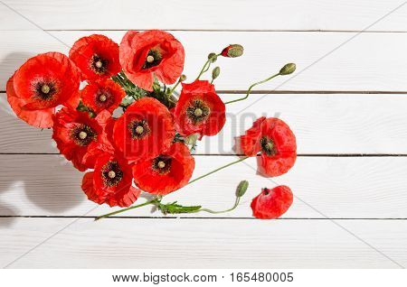 Bouquet Of Red Poppies In Glass Vase And Poppy Petals Near On Old White Wooden Table