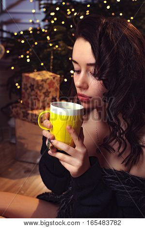 Innocent young brunet woman drinking the tea and waiting a Christmas in room with christmas tree