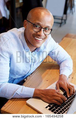 Black Businessman Sitting With Laptop