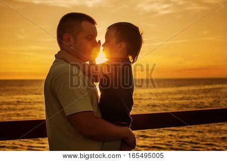 son with father on the sea at sunset