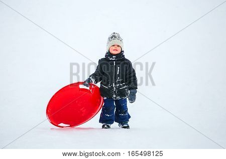 GRODNO BELARUS -JANUARY 15 : Boy riding the hills on sleds in winter JANUARY 15 2016 GRODNO BELARUS