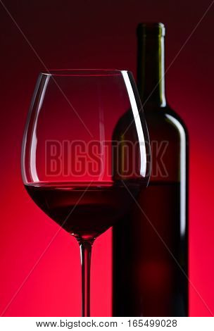 Glass And Bottle With Red  Wine On Red Background