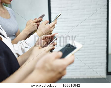 hands of young people sitting together playing with mobile phones.