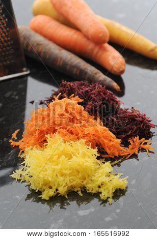 Grated fresh carrot. Yellow orange and purple.