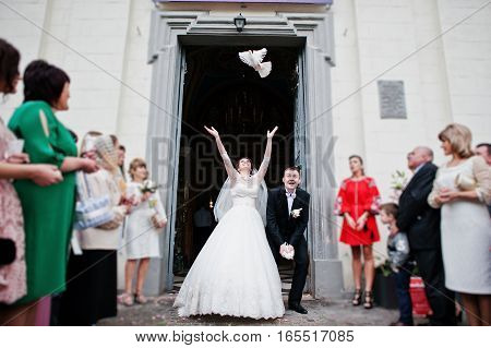 Happy Wedding Couple Puts In The Air Doves After Wedding Registration On Church. Blured Bokeh Effect
