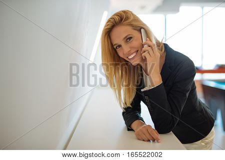 Portrait of a beautiful successful businesswoman talking on the phone in her company.