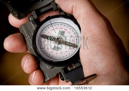 Hand of a hiker holding sighting compass