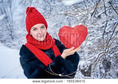 Love and valentines day concept. Closeup portrait of smiling woman showing red polygon paper heart shape over winter landscape