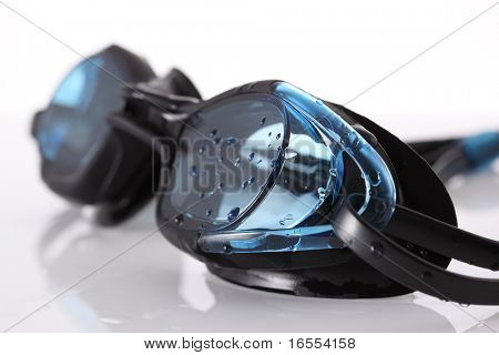 Wet blue swimming goggles on white background