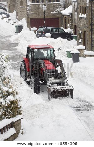 Tractor removing snow from a residential housing estate in winter