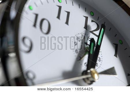 Close up of an alarm clock face showing 12 o'clock
