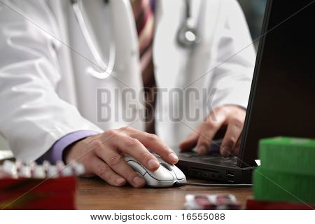 Doctor using a laptop computer to prepare an online prescription
