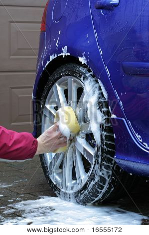 Cleaning the wheel on a blue car with a sponge