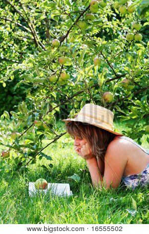 Young woman reading a book under an apple tree.