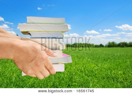 Hands Holding Stack of Books with Nature Background