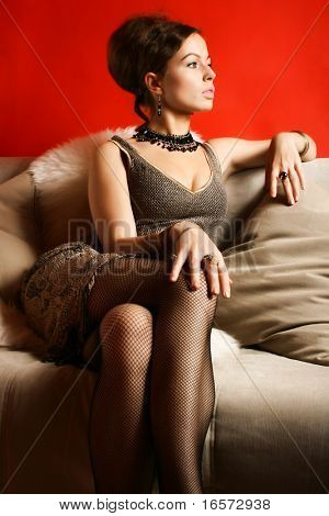 Portrait of woman in cocktail dress in interior on red background