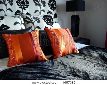 Orange Cushions On Black Bed