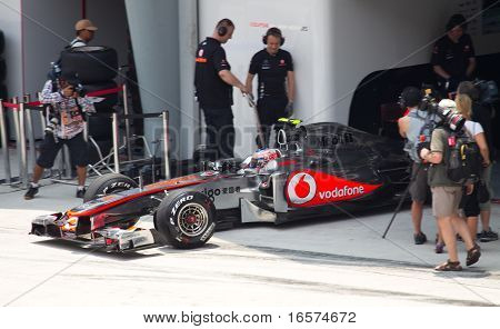 Jenson Button leaves the pit garage for friday practice