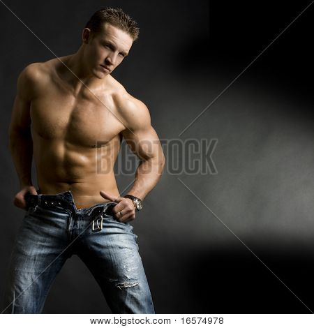 Beautiful young man posing on dark background