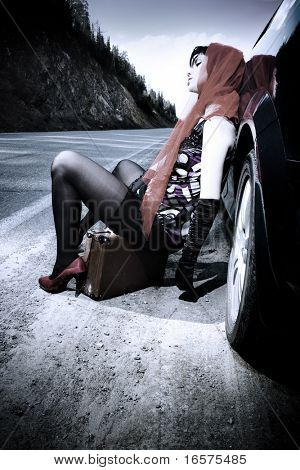 beautiful woman with baggage near the car