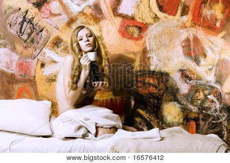portrait of young blond woman in bed on art background